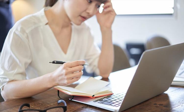 パソコンの前で悩む女性の写真